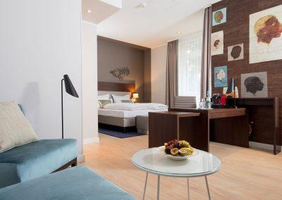 Mercure Hotel Köln Belfortstraße Apartment Blick von Couch auf Bett und Schreibtisch